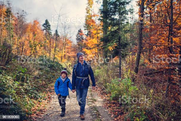 Photo of Father and son hiking in autumn forest