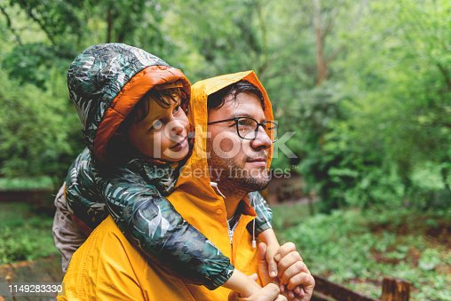 Father and son having fun on rainy day