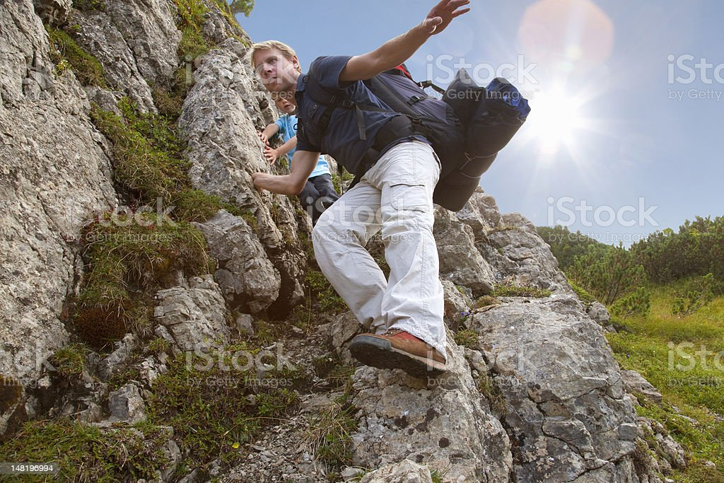 Father and son hiking on rocky terrain stock photo