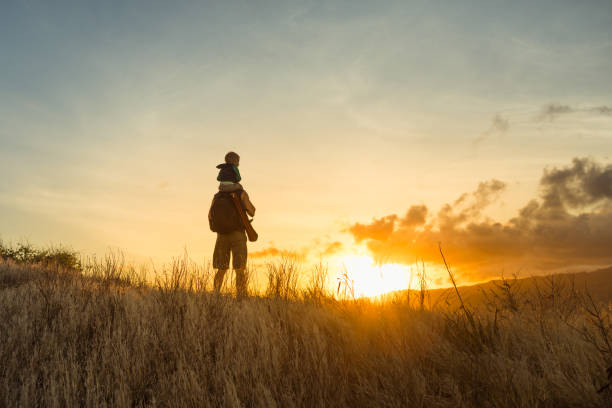 Father and son hiking through the mountain at sunrise stock photo