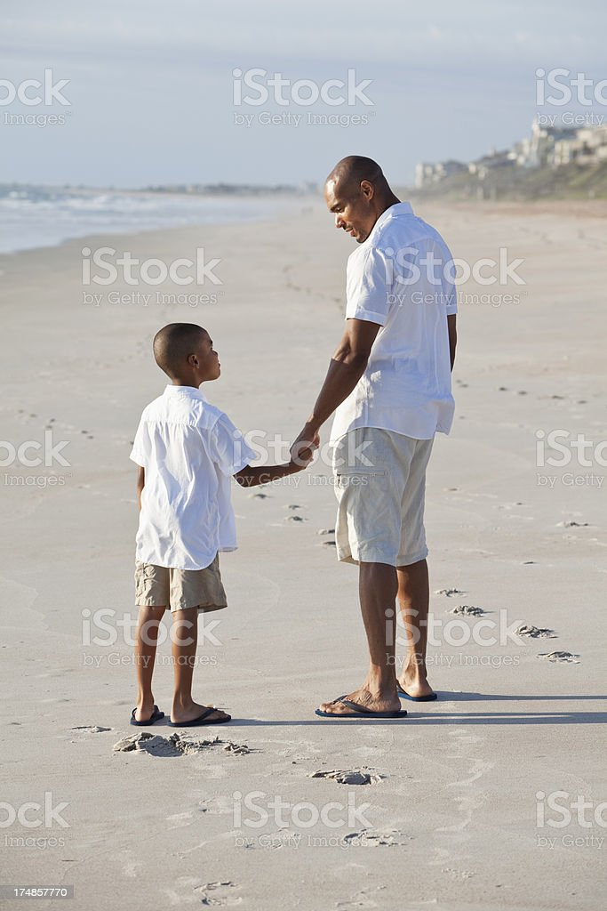 Father and son holding hands at the beach royalty-free stock photo