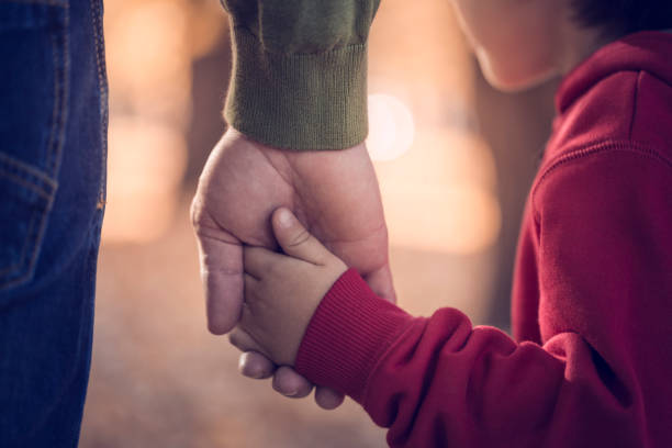 Father and son holding hands in park stock photo