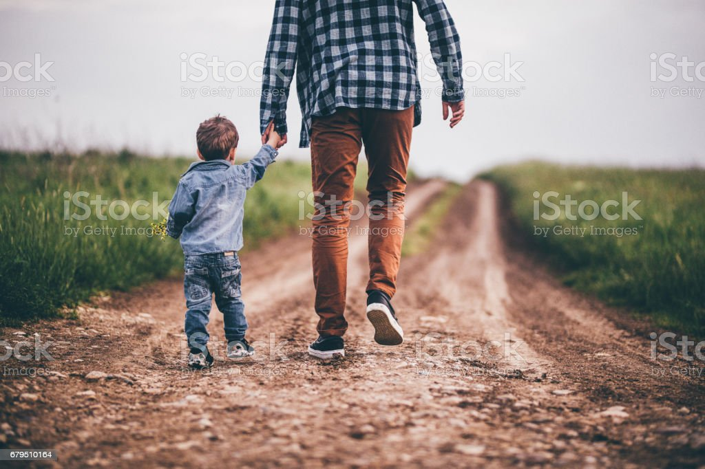 Father and son holding hands stock photo