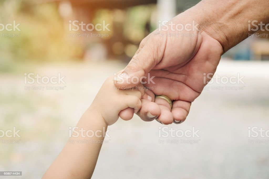 Father and son holding hands together. – Foto