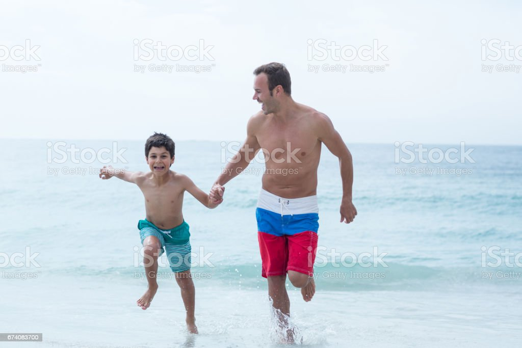 Father and son holding hands while running at beach foto de stock royalty-free