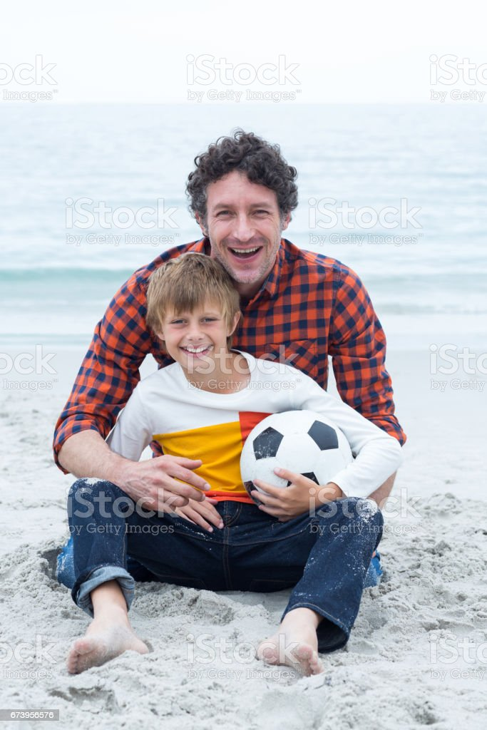 Father and son holding soccer ball while sitting at beach royalty-free stock photo