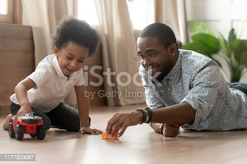 African father play together with little son people lying on warm comfort heated floor holding toy car truck competing in races having fun, boyish games, entertaining activity with kid at home concept