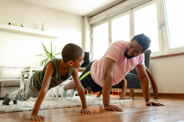 Father and son, home exercising stock photo