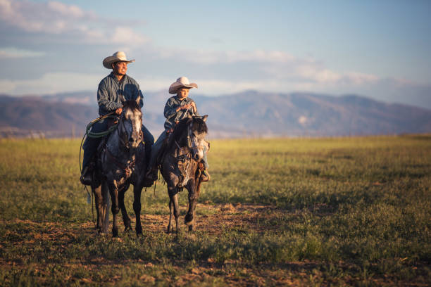 Father and son horseback riding Father and son horseback riding rancher stock pictures, royalty-free photos & images