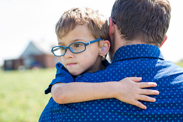 father and son hugging on outdoor summer - handicap photos et images de collection