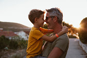 istock Father and son hugging outdoors, shallow depth of field 1268441898