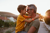 istock Father and son hugging outdoors, shallow depth of field 1268441899