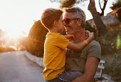 istock Father and son hugging outdoors, shallow depth of field 1268445447
