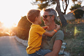 istock Father and son hugging outdoors, shallow depth of field 1268445452