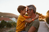 istock Father and son hugging outdoors, shallow depth of field 1268445455