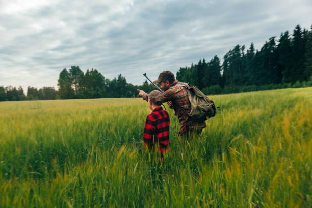 père et fils de chasse pour le sanglier - chasseur photos et images de collection