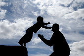 Son jumping into the arms of his father, silhouetted to create dramatic effect