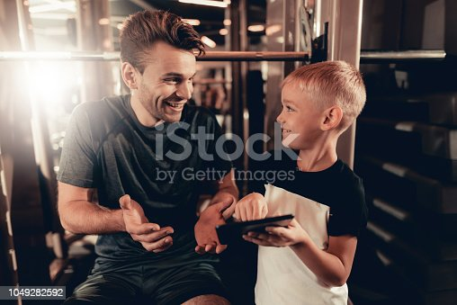 997711042istockphoto Father And Son In Gym. Information On Tablet. 1049282592