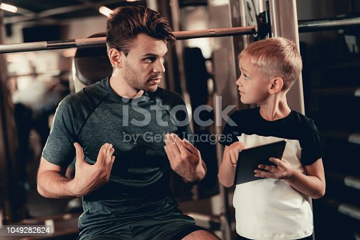 997711042istockphoto Father And Son In Gym. Information On Tablet. 1049282624