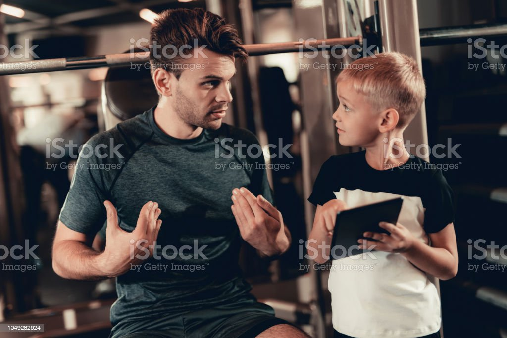 Father And Son In Gym. Information On Tablet. stock photo