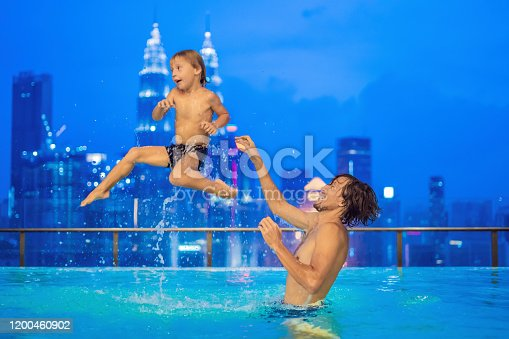535761281 istock photo Father and son in outdoor swimming pool with city view in blue sky 1200460902
