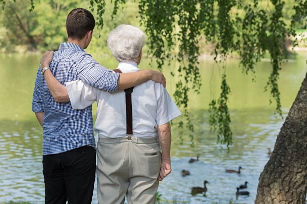 vater und sohn im park - senior bilder wasser stock-fotos und bilder