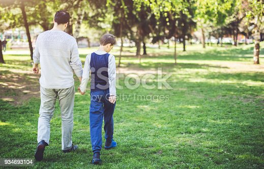 Father and son holding hands and walking through park on a sunny day. Parenthood, childhood, autism awareness concept.