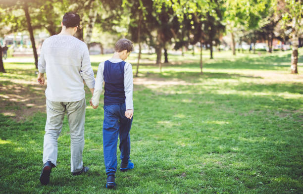 father and son in park - autism stock photos and pictures