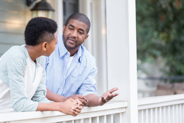Father and son in serious front porch conversation stock photo