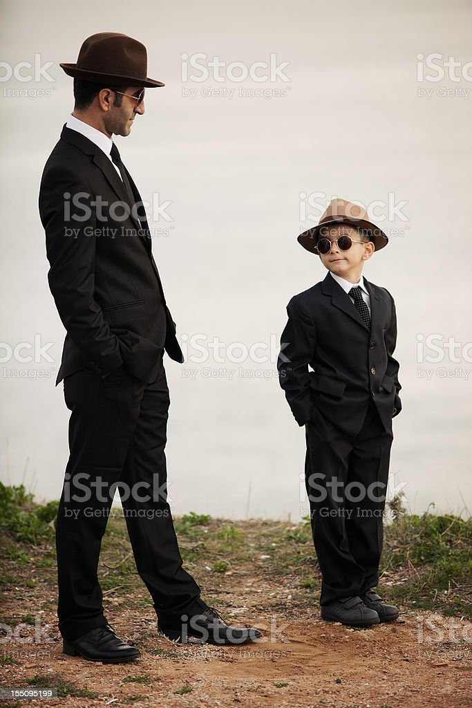 Father and son in similar clothes, outdoor ,day light, vertical royalty-free stock photo