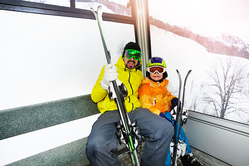 Father and son in ski lift cabin