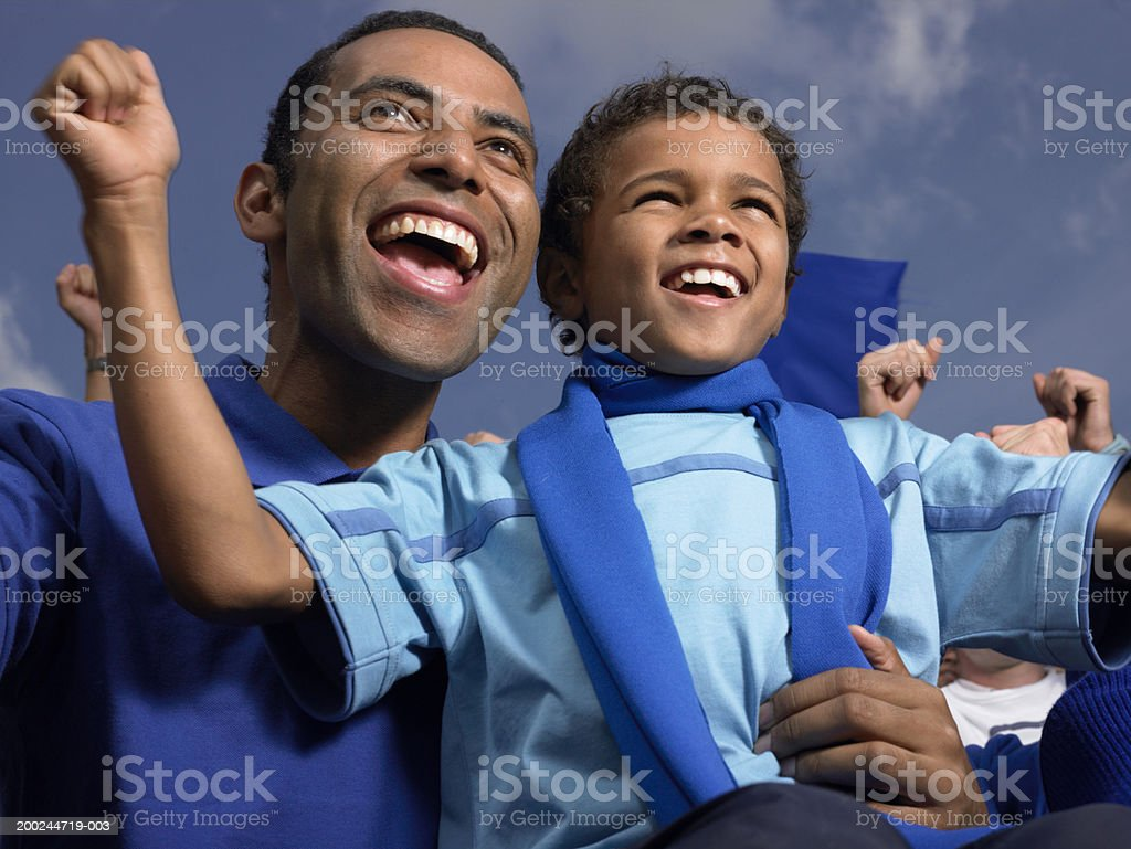 Father and son (5-7) in stadium crowd, cheering, close-up stock photo