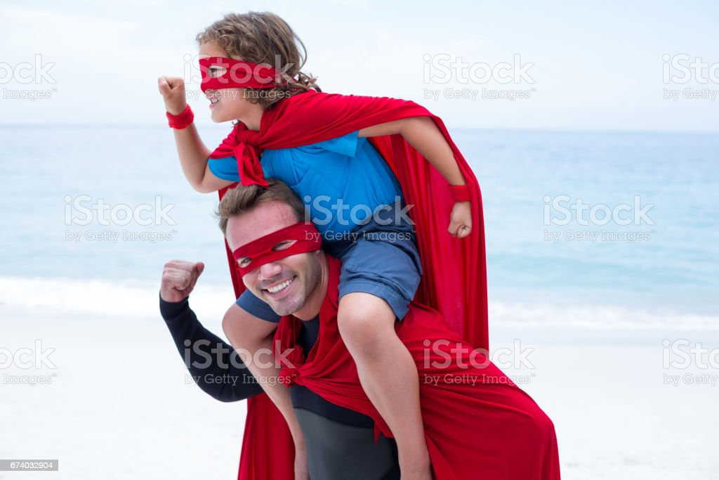 Father and son in superhero costume pretending to run royalty-free stock photo