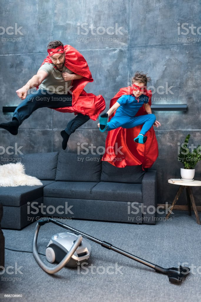 father and son in superhero costumes jumping on sofa at home royalty-free stock photo