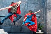父と息子の自宅のソファの上にジャンプのスーパー ヒーロー衣装