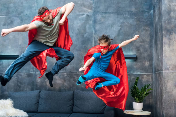 father and son in superhero costumes jumping on sofa at home stock photo