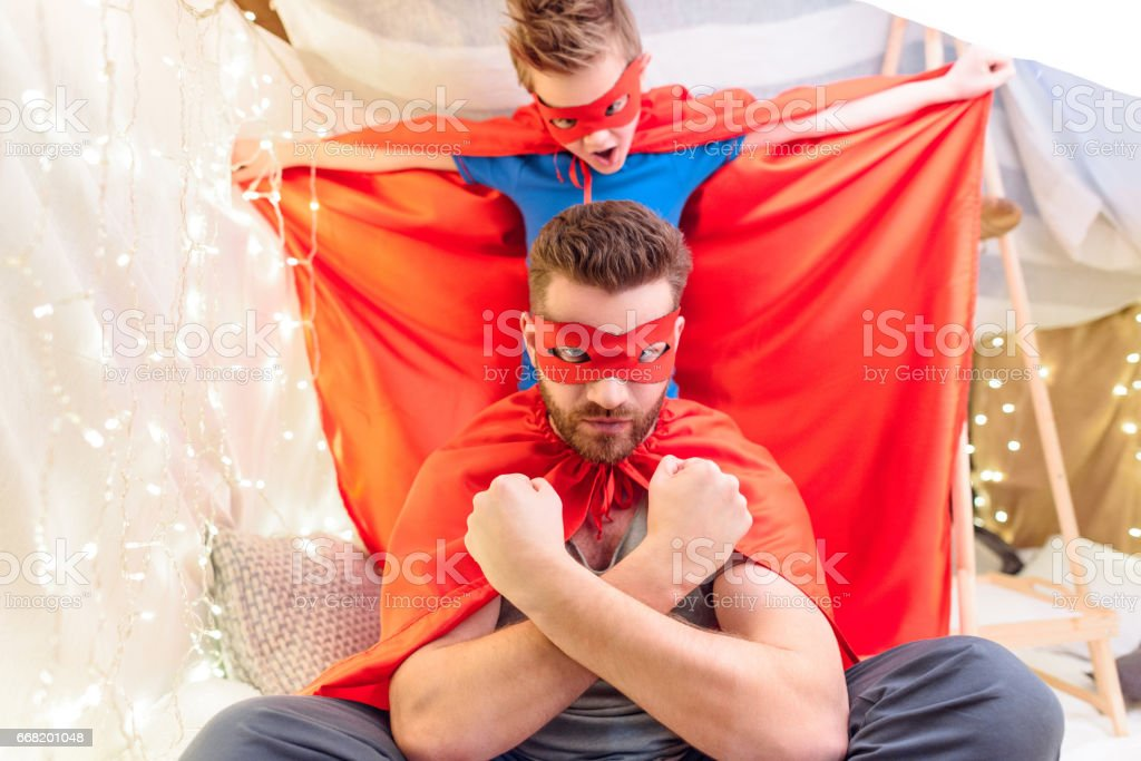 Father and son in superhero costumes playing together in blanket fort stock photo