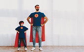 Father And Son. Red And Blue Superhero Suits. Masks And Raincoats. Posing In A Bright Room. Young Happy Family Holiday Concept. Resting Together. Save The World. Get Ready. Arms Akimbo.