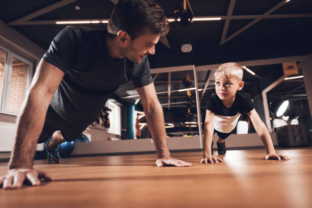 Father and son in the gym. Father and son spend time together and lead a healthy lifestyle. stock photo