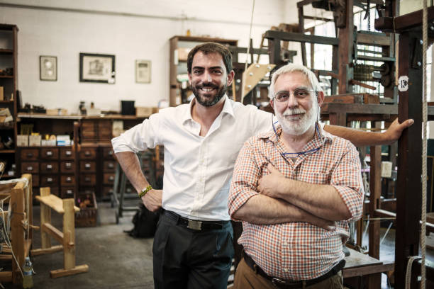 Father and son in their artisanal handicraft traditional textile factory stock photo