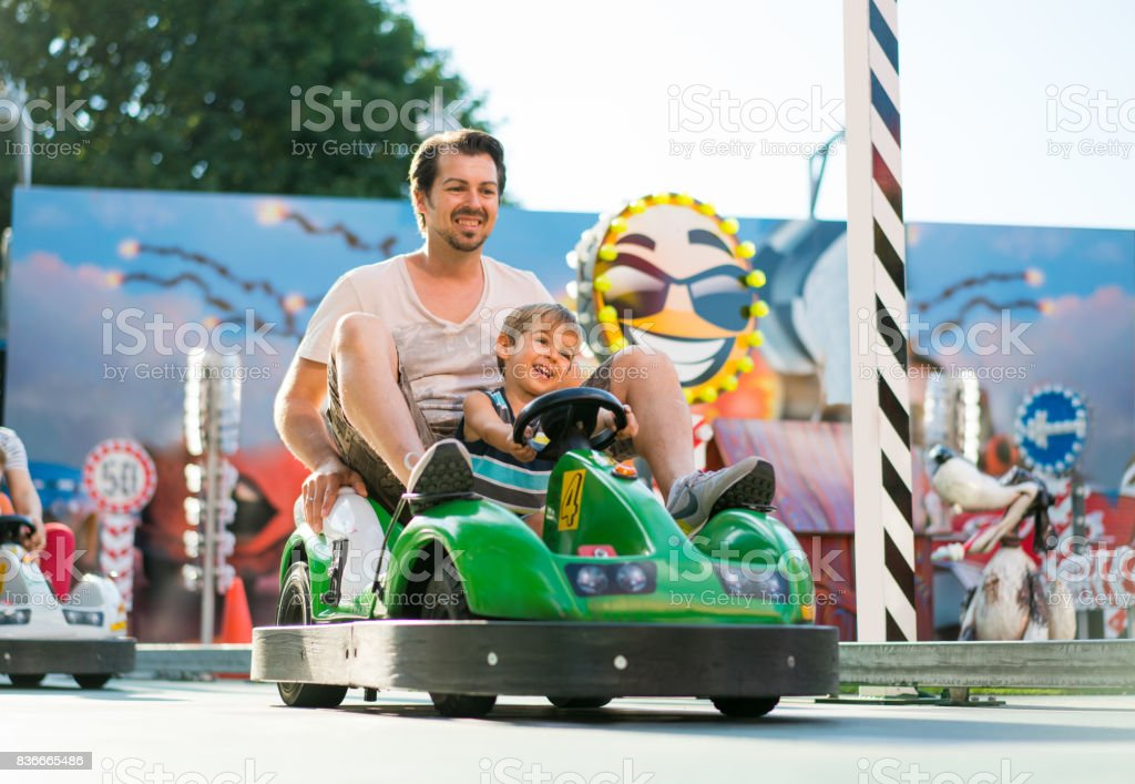 father and son in toy car stock photo