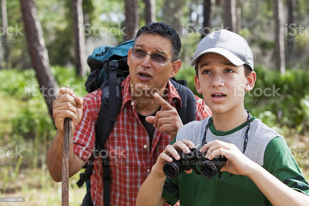 Father and son in woods with binoculars stock photo