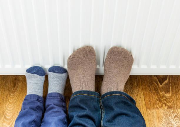 Vater und Sohn in Wintersocken aus Wolle wärmen ihre Füße in der Nähe der Heizkörper. – Foto