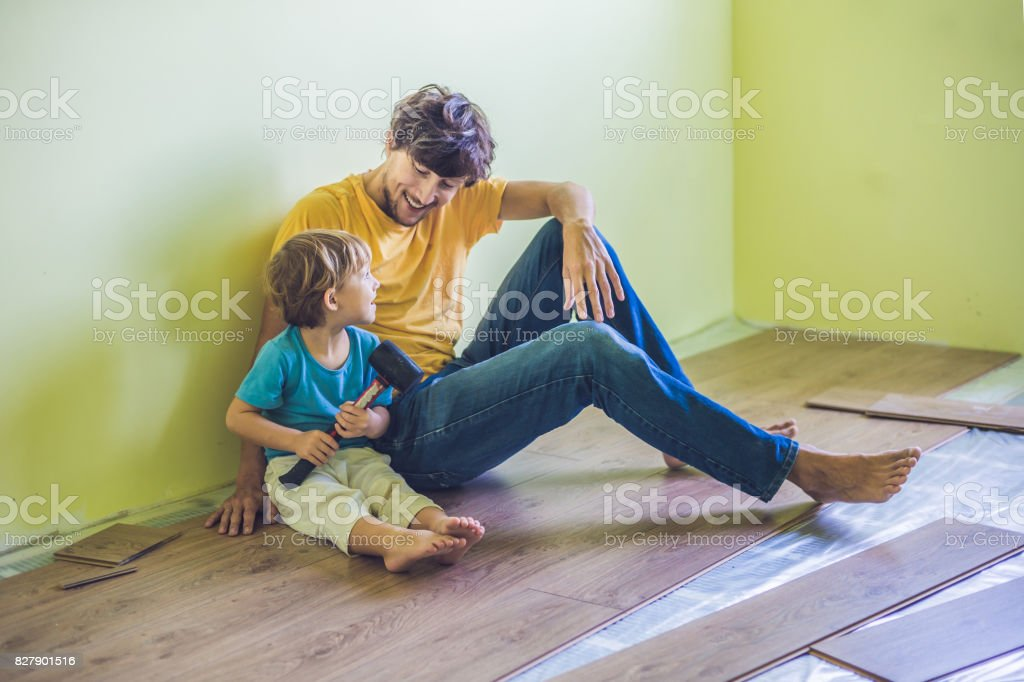 Father And Son Installing New Wooden Laminate Flooring Infrared
