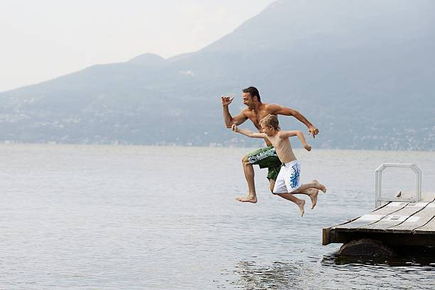 Father and son jumping from dock stock photo