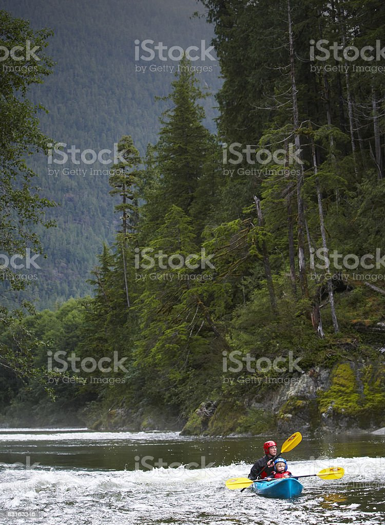 Father and son kayaking down river. royaltyfri bildbanksbilder