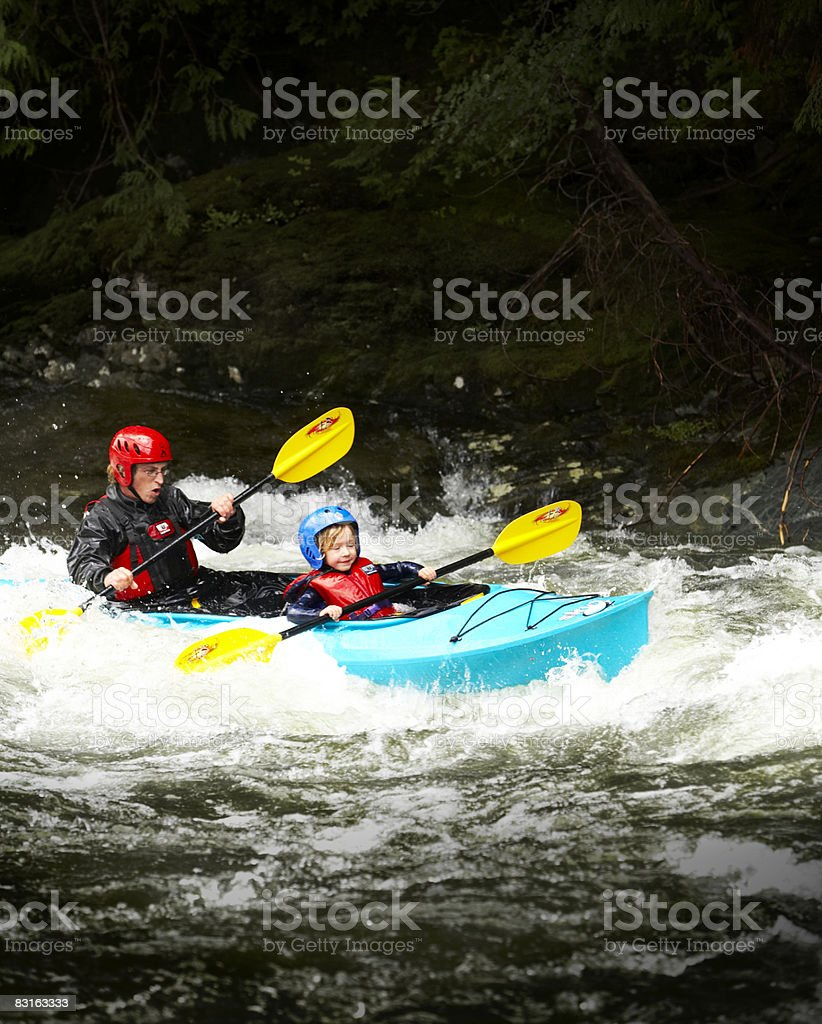 Father and son kayaking through rapids. royalty free stockfoto
