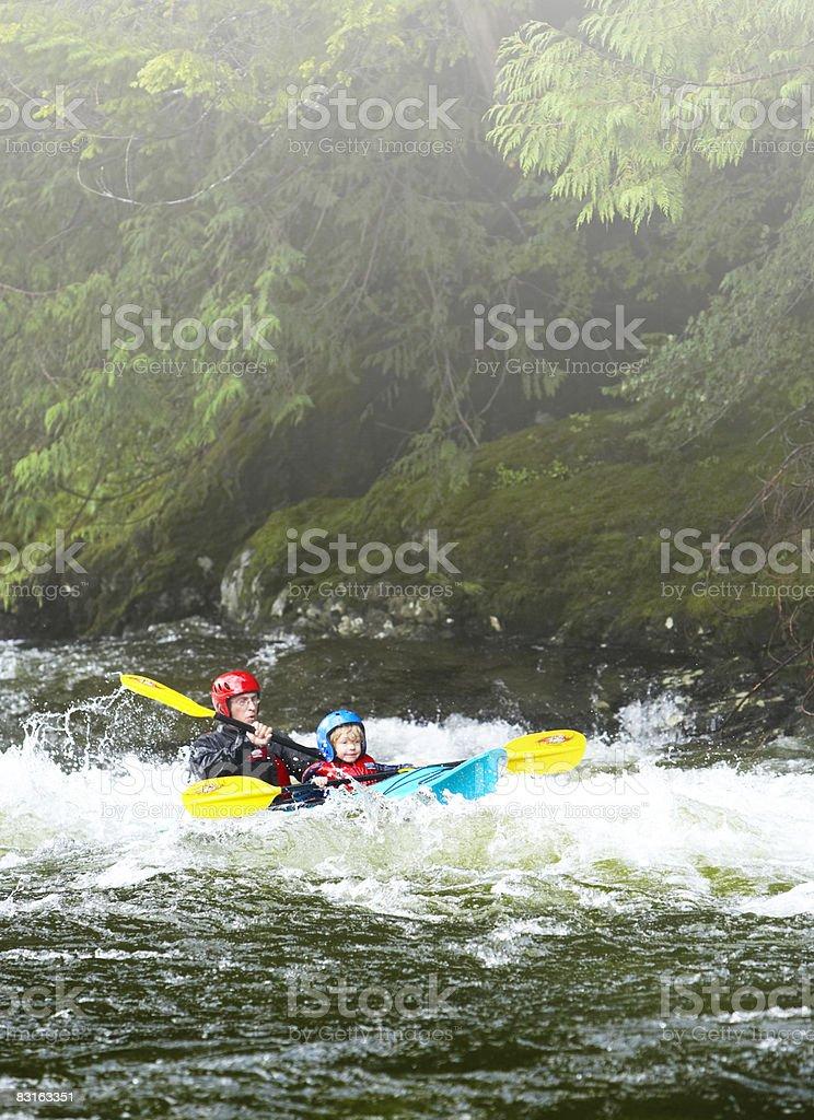 Padre e figlio in kayak attraverso le rapide. foto stock royalty-free