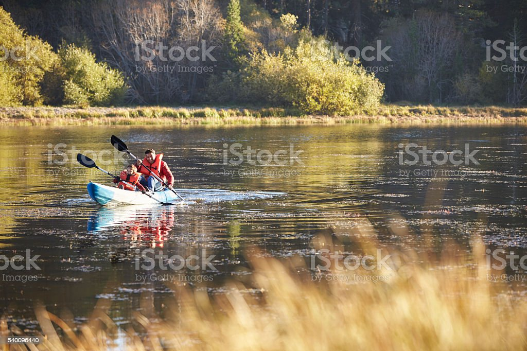 Father and son kayaking together on a lake, front view stock photo
