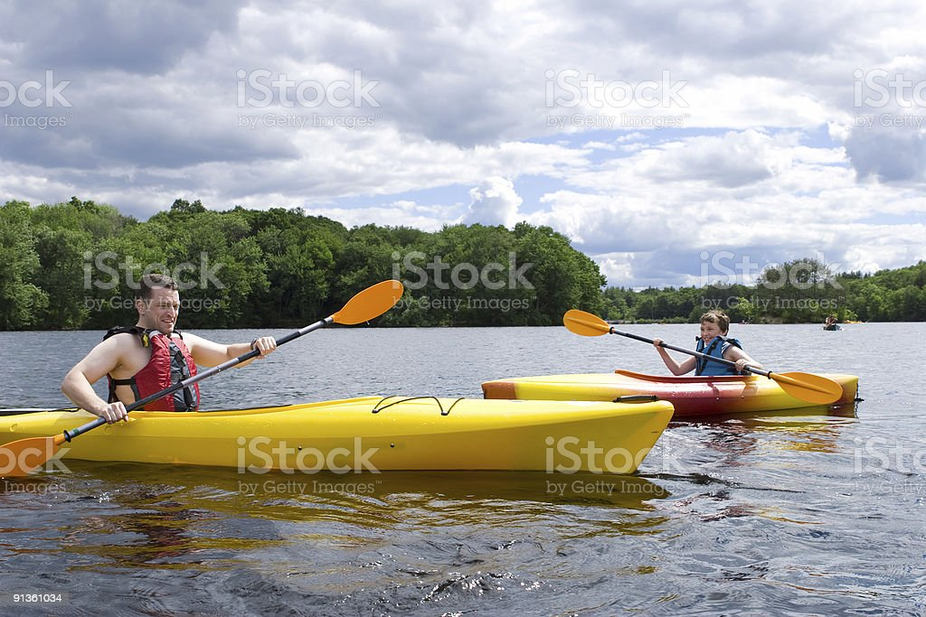 Father and son kayaking together on a lake royalty-free stock photo